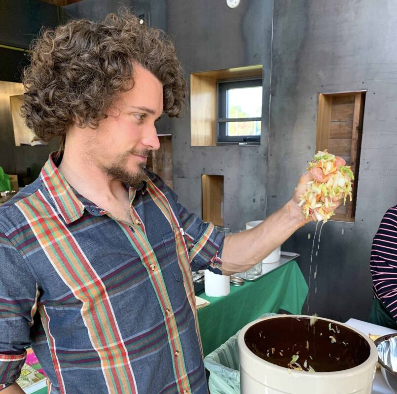 Community Cultures instructor Trevor Ring teaching a fermentation workshop, holding dripping cabbage in his hand.